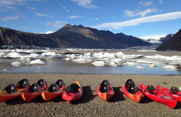 Photo de kayaks posés sur la rive du lagon aux icebergs