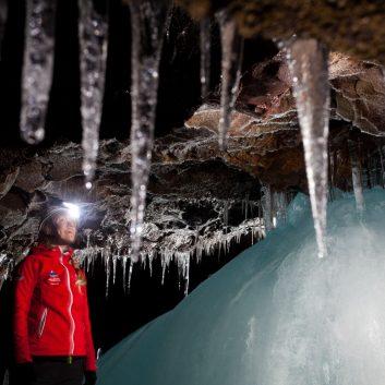 Une personne observe avec émerveillement l'intérieur d'une grotte de lave en Islande