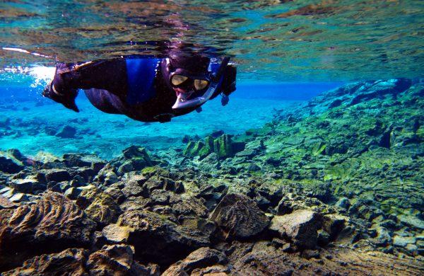 Un snorkeleur dans la faille de Silfra en Islande
