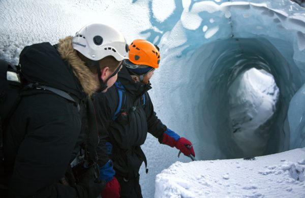 Deux hommes regardant dans une crevasse sur un glacier en Islande