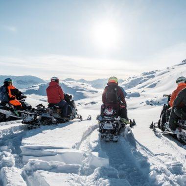 Groupe de peronnes en motoneige sur un glacier