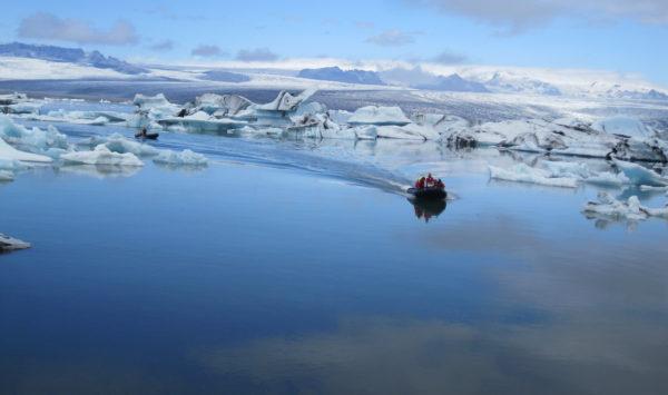 Photo aérienne d'un zodiac de face dans le lagon aux icebergs
